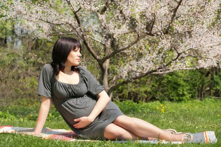 expectant mother is having a rest under blossom apple tree, solar springtime Stock Photo - 3271963