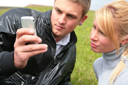 gay in black jacket and blond girl look at device photo