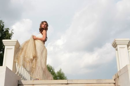 retro style  portrait of the beautiful girl in white gown on background cloudy sky