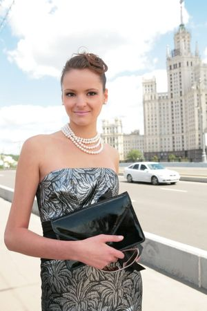smiling girl in black-silvery dress on background of the old moscow skyscraper Stock Photo - 3381014
