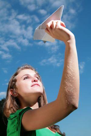 splendid: young girl starts paper plane in blue sky