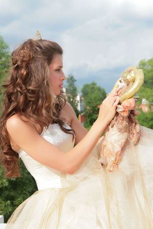 splendid: princess in white-golden gown plays with loved doll on background cloudy sky