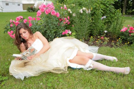 princess in white-golden gown reads book under rosebushes photo