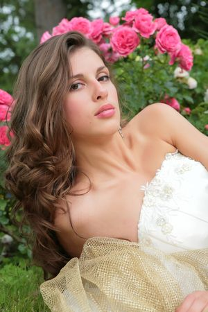 portrait of the beautiful girl in white-golden gown on background of the rosebush Stock Photo