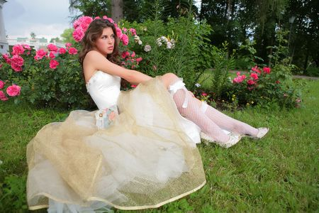 rosebush: beautiful girl in wedding white-golden gown sits on herb in town park under rosebush
