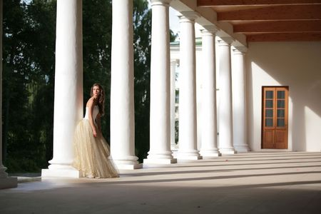 girl in white-golden gown of the bride amongst colonnades of the old-time building Stock Photo