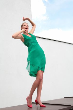girl in green dress and red loafer dances on winds photo