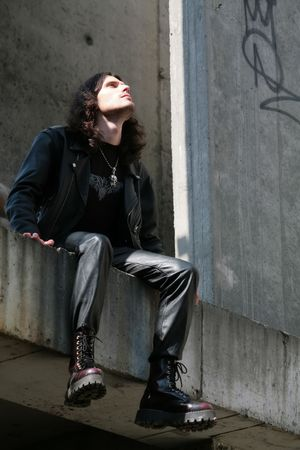 man in black leather cloth sits amongst concrete gray surfaces photo