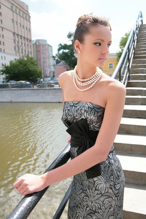 banisters: luxurious brunette beside banisters on bridge through channel with water Stock Photo