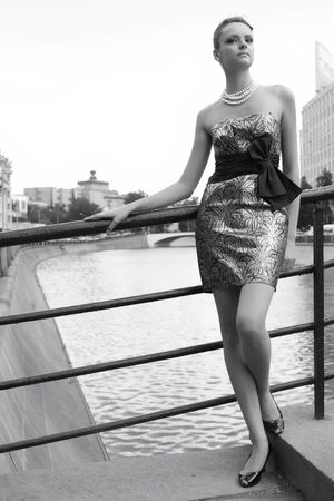 banisters: girl in silvery dress and long legs near metallic banisters of the bridge through channel with water