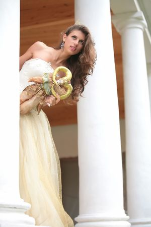 peers: beautiful girl in gown of the bride with doll peers out from behind pillar