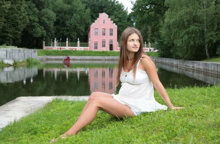 beautiful womb: romantic portrait of the pregnant young woman in town park near water