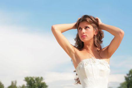 splendid: beautiful girl in wedding gown on background blue sky