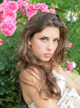 rosebush: portrait of the beautiful girl in white gown on background of the rosebush