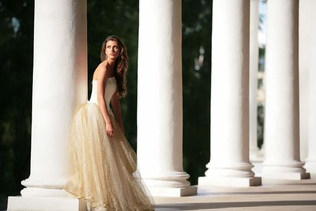 splendid: colonnade of the old-time building and beautiful girl in white-golden gown of the bride Stock Photo