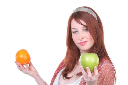 girl makes a choice between orange and apple with copy-space photo