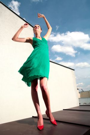 splendid: girl in green dress and red loafer dances on celestial background with cloud Stock Photo