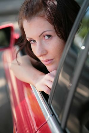 close-up portrait of the beautiful girl in red car photo