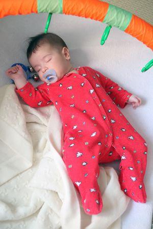 sweetly: infant in red cloth sweetly sleeps