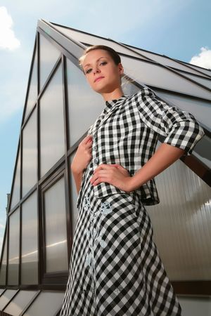girl in plaid dress in style 50-60h on background of the glass-metallic pyramid photo