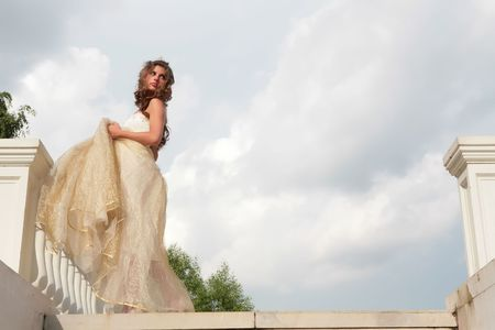 vintage style portrait of the beautiful girl in white-golden gown on background cloudy sky Stock Photo - 3938895