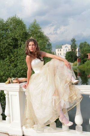 banisters: real princess in white-golden gown sits on banisters its palace
