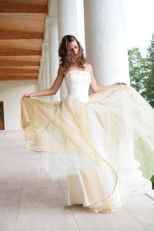 sposa in abito bianco-oro balli tra pilastri Archivio Fotografico