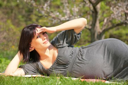 horizontal portrait of the pregnant woman lying on herb in blossom garden Stock Photo