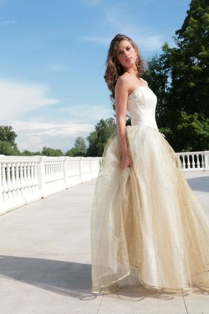 splendid: pretty princess in white-golden gown under blue sky