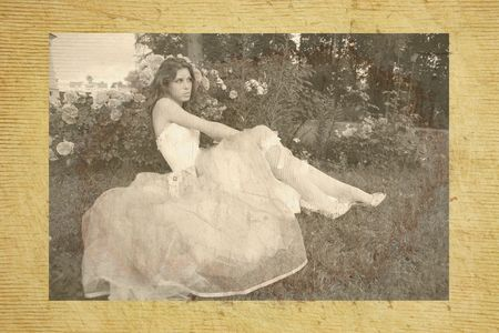rosebush: vintage portrait of the beautiful girl in white gown on background of the rosebush