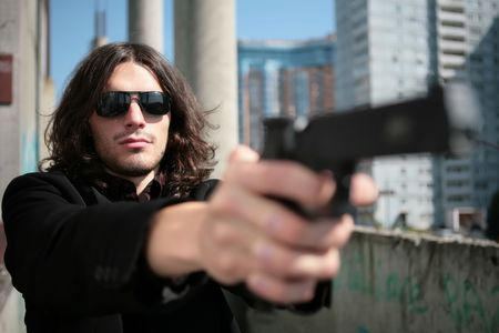 unkind: young man with gun in image of the killer in style of the italian film about mafia Stock Photo