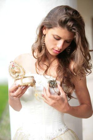 la bella ragazza in abito bianco-oro a guardare il dono