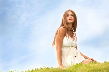 bella madre madre si siede su erba sotto cielo blu