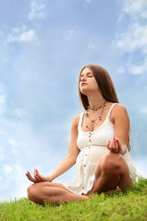 bella madre meditando � aperta sotto il cielo blu Archivio Fotografico