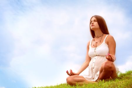 beautiful expectant mother is meditating on open air under blue sky photo