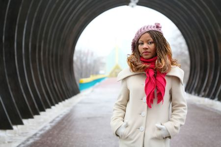 beautiful african girl in lilac beret, in light coat and bright red scarf photo