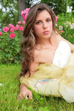 portrait of the pretty girl on background of the bush of the roses photo