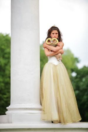splendid: beautiful bride in white-golden dress with loved doll dreams of future