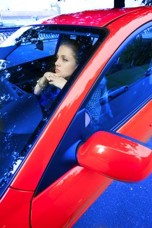 young woman in red car dreams of future photo
