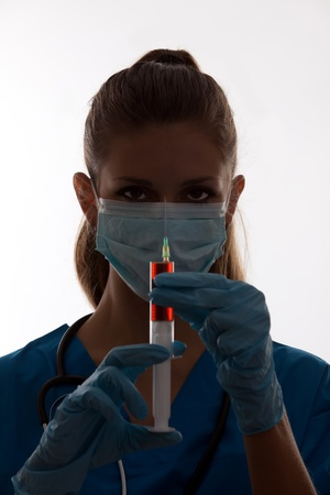 sterile: silhouette of a doctor with syringe on over white