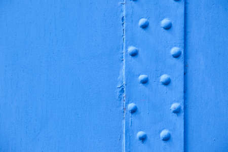 painted metallic blue background with rivets photo