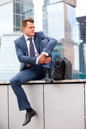 multi story: successful businessman resting on a background of office buildings Stock Photo
