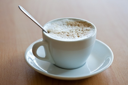 crema: white cup of coffee with crema on the wood table Stock Photo
