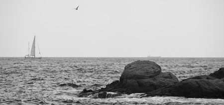 sea, rocks, and a sailboat, black and white photo, grain photo