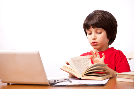 little boy in red t-shirt with computer and textbooks on white background Stock Photo