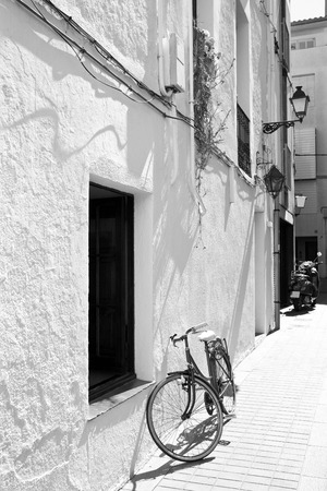 a two wheeled vehicle: Spanish town street with a bicycle at a white wall, black and white photo Stock Photo