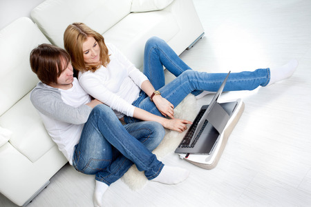 Couple relaxing at home near sofa photo