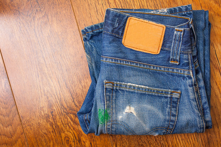 full of holes: old blue jeans with brown label on the belt smeared with green paint and a pocket full of holes, which were stored for a long time a mobile phone Stock Photo