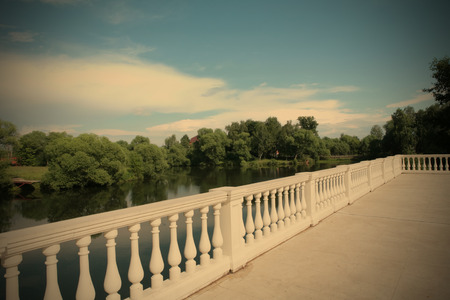balustrade: white balustrade ashore calm river under blue sky