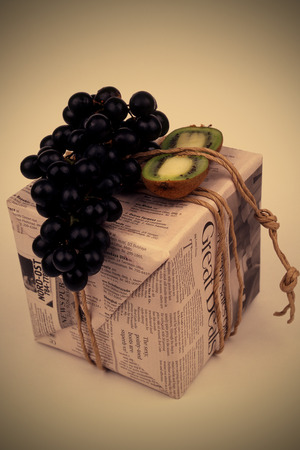 oude krant: gift, stylishly packaged in an old newspaper box tied with twine with black grapes and kiwi Stockfoto
